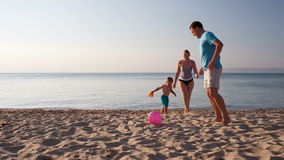 Young family playing football on the beach. Young family frolicking together playing football soccer on the beach at sunset with the little boy running with his