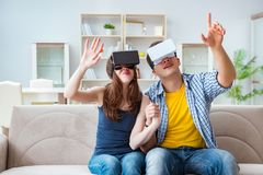 The young family playing games with virtual reality glasses. Young family playing games with virtual reality glasses Royalty Free Stock Photo