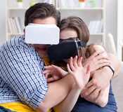 Young family playing games with virtual reality glasses royalty free stock images