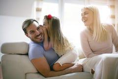 Whispering secret. Family at home. stock photos