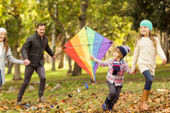 Young family playing with a kite Stock Photos