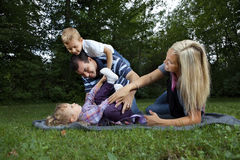Young family playing at a park stock photography