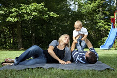 Young family playing at a park. (baby boy only Royalty Free Stock Photos