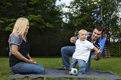 Young family playing at a park. (baby boy only Royalty Free Stock Images