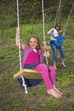 Young family playing on swings Stock Photos