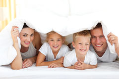 Young Family Playing Together On A Bed Royalty Free Stock Images