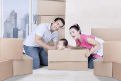 Young family plays with boxes in the apartment Royalty Free Stock Images