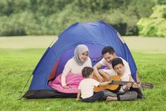 Young family plays a guitar in the campground. Picture of young family playing a guitar while enjoying their holiday in the campground royalty free stock photos