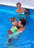 Young family in the pool. Young family with one child in the pool Stock Image