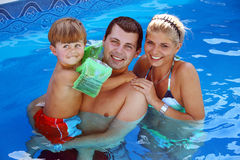 Young family in the pool. Young family with one child in the pool Stock Images