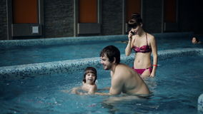 Young family in the pool teaching his son to swim. A boy jumps into the water. stock video