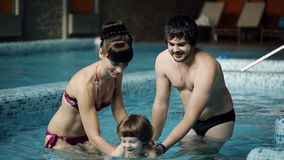 Young family in the pool teaching his son to swim. Family swimming in the pool. stock video footage