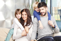 Young family. Portrait of happy young family with two kids sitting at sofa and smilig. Happy father giving piggyback to his cute son Stock Image