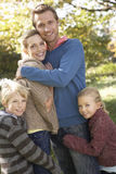 Young family pose in park Royalty Free Stock Photography