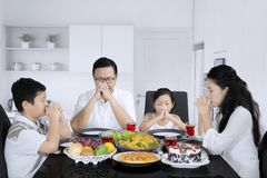 Young family praying before meals in the kitchen royalty free stock photos