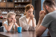 Young family praying. While sitting at the table in kitchen Stock Photo