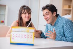The young family in pregnancy planning concept with ovulation calendar. Young family in pregnancy planning concept with ovulation calendar stock image