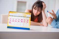 The young family in pregnancy planning concept with ovulation calendar. Young family in pregnancy planning concept with ovulation calendar stock photo