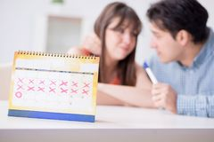 Young family in pregnancy planning concept with ovulation calend. Ar stock image