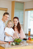 Young family preparing salad Royalty Free Stock Photos