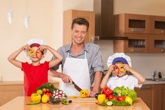 Young family preparing salad together. Royalty Free Stock Photos