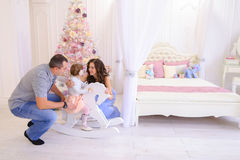 Young family preparing for upcoming in spacious bedroom light on. Happy European family, young parents and young child in good mood to decorate Christmas tree stock image