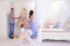 Young family preparing for upcoming in spacious bedroom light on. Happy European family, young parents and young child in good mood to decorate Christmas tree royalty free stock image