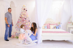 Young family preparing for upcoming in spacious bedroom light on. Happy European family, young parents and young child in good mood to decorate Christmas tree royalty free stock photos