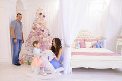 Young family preparing for upcoming in spacious bedroom light on. Happy European family, young parents and young child in good mood to decorate Christmas tree stock photography