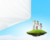 Young family pulling banner. Father and son pulling blank banner. Place for text Stock Photo