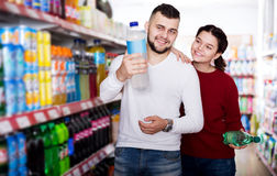 Young family purchasing soft dinks. Smiling young family purchasing soft dinks at food store Stock Images