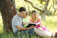 Young family reading the Bible. In nature Royalty Free Stock Images