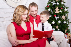 Young family reading book in front of Christmas tree Royalty Free Stock Photography