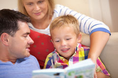Young family reading a book together Royalty Free Stock Photography