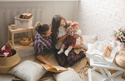 Young family reading story indoors Royalty Free Stock Photo
