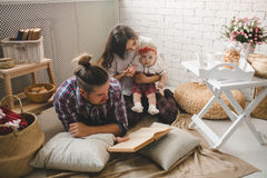 Young family reading story indoors Royalty Free Stock Images