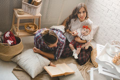 Young family reading story indoors Royalty Free Stock Photography