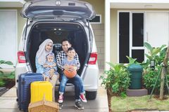 Young family ready for a vacation. Picture of young family ready for a vacation while looking at the camera and sitting together in the car trunk. Shot in the Stock Photos
