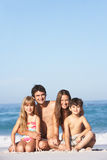 Young Family Relaxing On Beach Holiday. Smiling At Camera royalty free stock photos