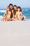 Young Family Relaxing On Beach Holiday. Smiling At Camera stock images