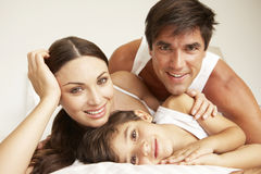 Young Family Relaxing On Bed Stock Photography