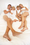 Young Family Relaxing In Bed Together Stock Photography