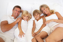 Young Family Relaxing In Bed Together Royalty Free Stock Photography