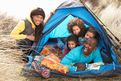 Young Family Relaxing Inside Tent On Holiday. Young Family Relaxing Inside Tent On Camping Holiday stock photography