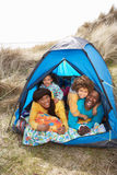Young Family Relaxing Inside Tent On Holiday. Young Family Relaxing Inside Tent On Camping Holiday royalty free stock photo
