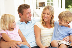 Young Family Relaxing Together On Sofa Stock Photos