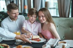 Young family in a restaurant. Young family with a child dining in a restaurant stock photography