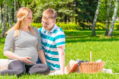 Young family resting in a park at a picnic. The girl with a big pregnant belly Royalty Free Stock Photos