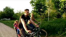 Young Family Riding Bicycles In Green Park stock footage