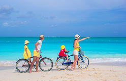 Young family riding bicycles on tropical beach Royalty Free Stock Photos